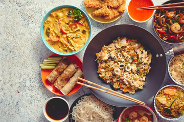 Traditional Chinese or Thai food set. Chinese noodles, fried rice with chicken, tom yum soup, spring rolls, deep fried fish and udon with shrimps. Top view. Asian style food concept.