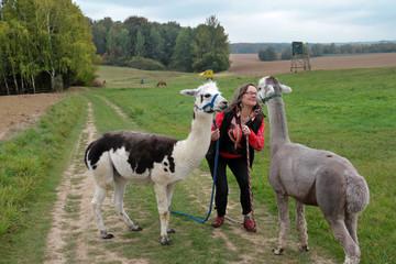 Lächelne Frau 50plus mit Alpakas in der Landschaft - Vicugna pacos - Therapietier - Alpakatherapie