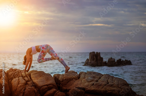 Woman Playing Yoga Pose On Sea Coast Against Beautiful Sun Rising