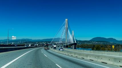 Port Mann Bridge, very little traffic, broad daylight on a blue sky.