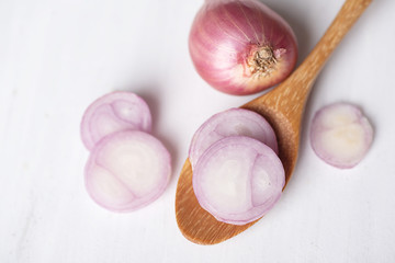 Sliced red shallot onion on wooden spoon, herb and spice, food ingredient