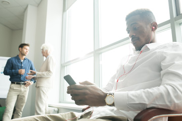 Serious relaxed young African employee in earphones listening to music and using smartphone while sitting on chair in office