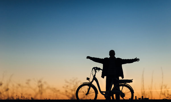 Silhouette of the male cyclist on the e-bike or electric bicycle on the sunset background. The man spread his arms to the side. Active pension. Relaxation. Travel. Sport.