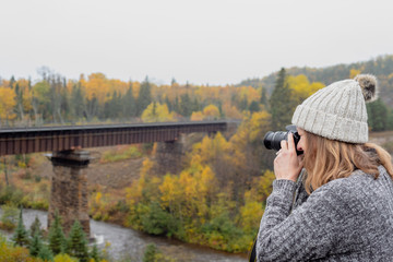woman taking photo of bridge over river in Ontario Canada