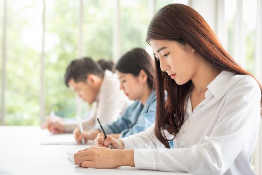 woman sitting in a row having a test in paper