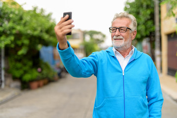 Happy handsome senior bearded man smiling while taking selfie pi