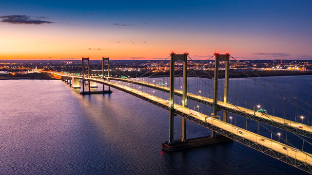 Aerial view of Delaware Memorial Bridge at dusk. The Delaware Memorial Bridge is a set of twin suspension bridges crossing the Delaware River between the states of Delaware and New Jersey