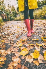 Red rubber boots woman walking in autumn leaves street in park. Fall fashion lifestyle.