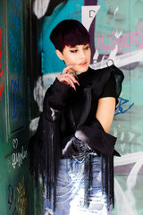 Portrait of a stylish fashion model with short purple hair standing on a city street