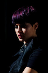 Close up portrait of a stylish fashion model with short purple hair looking down