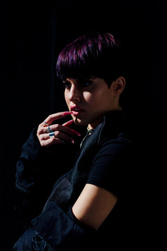 Portrait of a sunlit fashion model with short purple hair and long nails touching chin