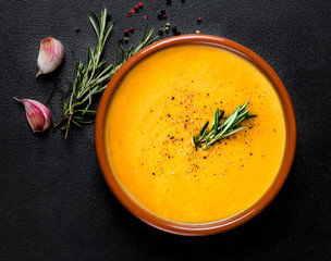 Pumpkin and carrot  Cream soup on  black board  background. Autumn cream-soup in country style. Top view. Copy space.