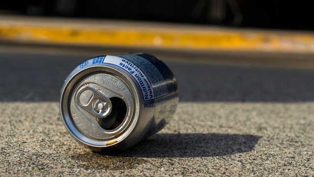 Close up of an empty can of coke, lien down on pavement.