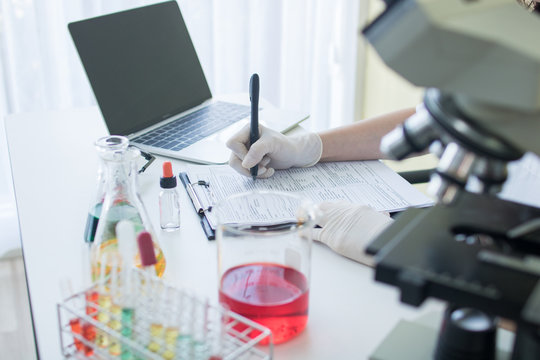researcher or scientist writing information result and note on paper in science lab