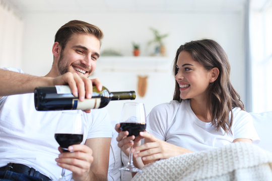 Young loving couple drinking a glass of red wine in their living room.