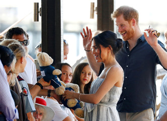 Britain's Prince Harry and Meghan, Duchess of Sussex, receive teddy bears as they greet members of the public in Kingfisher Bay on Fraser Island in Queensland