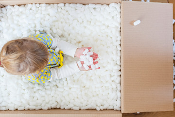 Kind spielt mit Verpackungsmaterial in Kiste. Child playing with with packaging material in packaging box.