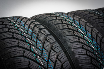 Winter car tires in row isolated on gray
