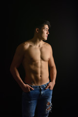 portrait of young man with  torso naked with jeans on black background