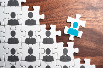 Personnel, employment and recruitment concept. Assembling jigsaw puzzle on wood desk.Human resource management. Creating successful organization.