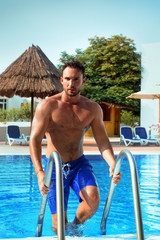 young handsome male bachelor with muscular torso enjoying swimming in pool. beautiful man with beard getting out of the pool wet with a sexy look in his eyes. Hot guy in pool is on vacation having fun
