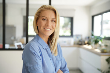 Attractive blond woman standing with arms crossed