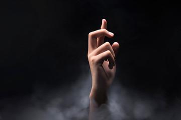 Hands finger with cross gesture over dark background