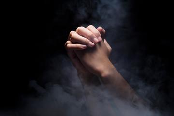 Praying hands over dark background