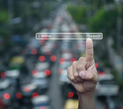 Hand pressing search www button over blur of rush hour with cars and road in city, Searching internet concept