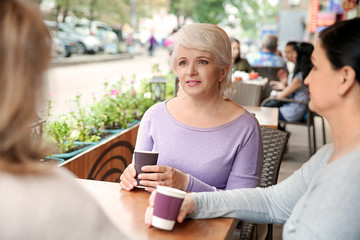 Beautiful mature women drinking coffee in cafe