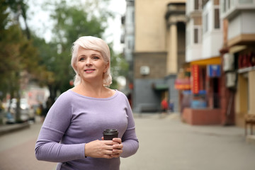 Beautiful mature woman drinking coffee outdoors