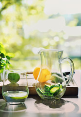 Glass of fresh cucumber water with jug on table