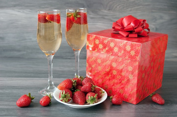 Chamopage in glasses with strawberries and gift in box with bow, new year card, chistmas card