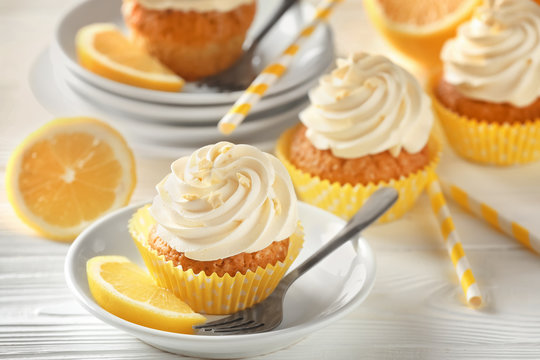 Plate with delicious lemon cupcake on white table