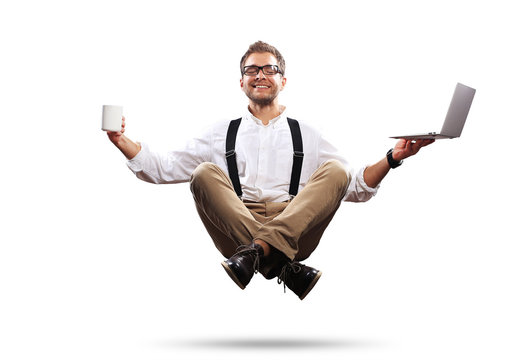 Young man is soaring in the air with a Cup of coffee and a laptop