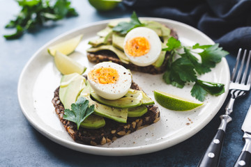 Healthy rye toast with avocado, egg, feta cheese on plate, closeup view. Breakfast, snack or lunch food