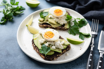 Healthy rye toast with avocado, egg, feta cheese on white plate. Healthy tasty breakfast, lunch or snack