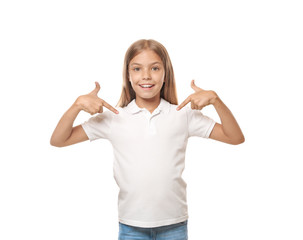 Little girl pointing at her t-shirt on white background