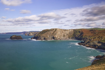 A scenic view of the west Cornwall coast taken From Barras Nose near Tintagel and Bossiney on a sunny Autumn day, using a slow shutter speed to blur cloud and water movement