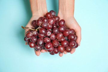Female hands with ripe tasty grapes on color background Fototapete