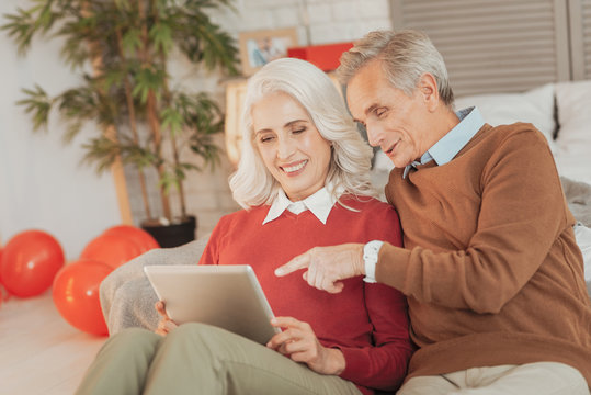 Interesting content. Happy elderly married couple sitting in the living room and viewing photos on the tablet while smiling joyfully and pointing at the tablet screen