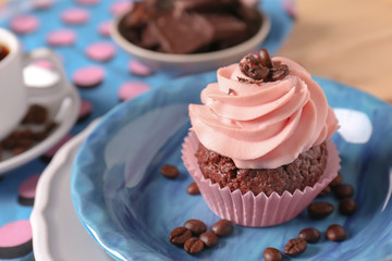 Plate with sweet cupcake and coffee beans, closeup