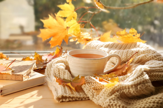 Cup of aromatic tea with warm plaid and autumn leaves on windowsill