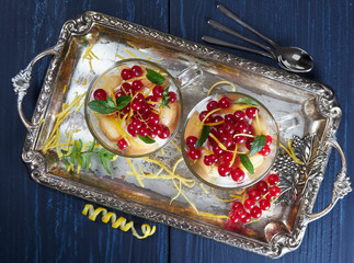 Two glass cups of limoncello (or limoncino) tiramisu topped with redcurrants and mint leaves, on a silver tray set on a dark background