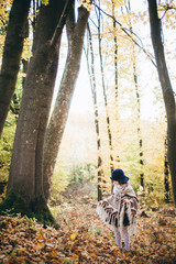 Outdoor portrait of a cute little girl in an autumn forest, wearing knitted poncho and hat. Autumn mood in the forest. Atmospheric walk through the forest of a beautiful girl