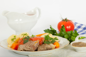 Boiled beef with creamy tomato sauce served with potatoes and carrots