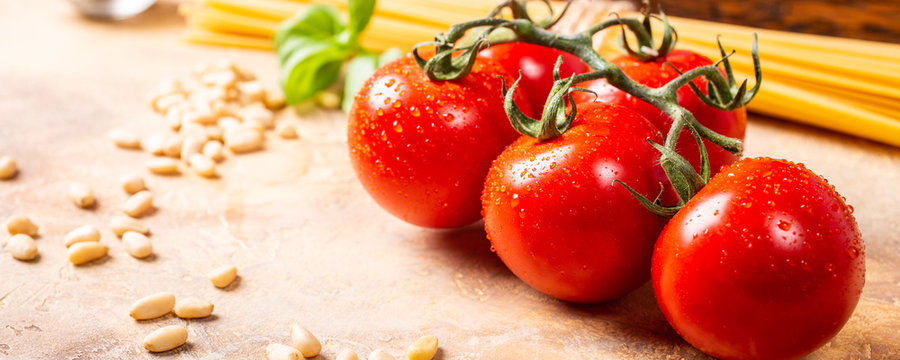 Fresh tomatoes for homemade classic italian pasta or pizza sauce with pine nuts and basil. Healthy food background. Banner.