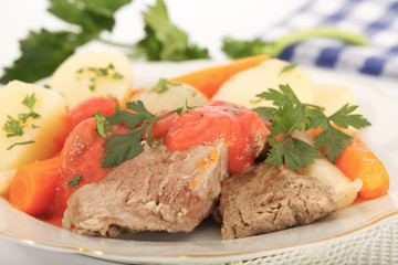Boiled beef with creamy tomato sauce served with potatoes and carrots, decorated with dill leaves