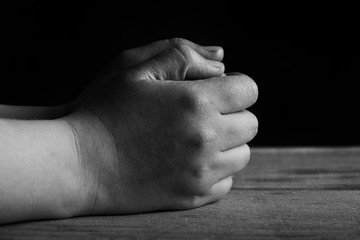 Hands of praying young man