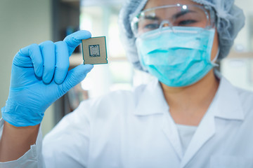 Portrait of computer engineer is holding CPU's computer for examination